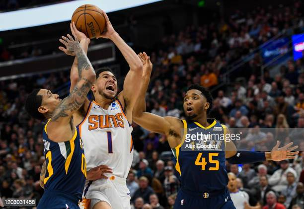 Devin Booker of the Phoenix Suns attempts a shot between Jordan Clarkson and Donovan Mitchell of the Utah Jazz during a game at Vivint Smart Home...