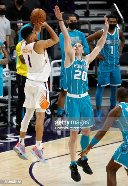 Devin Booker of the Phoenix Suns attempts a three-point shot over Gordon Hayward of the Charlotte Hornets during the final seconds of the NBA game at...