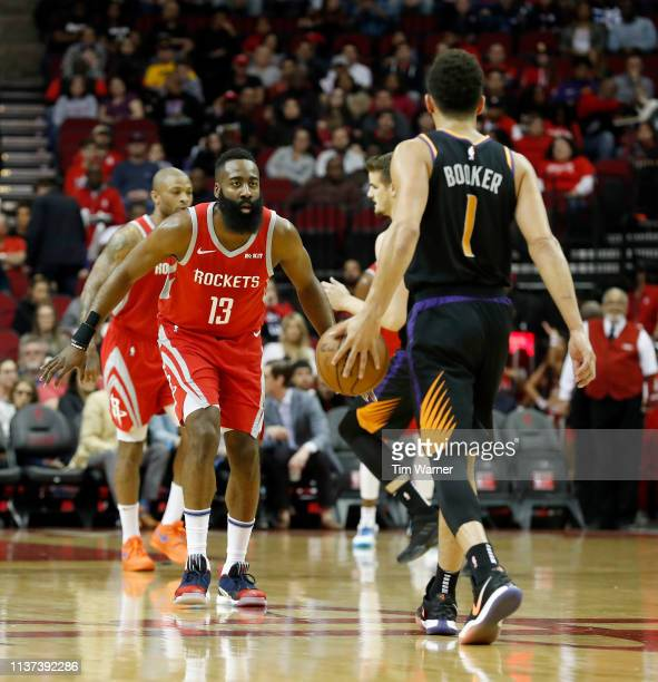 Devin Booker of the Phoenix Suns brings the ball up court defended by James Harden of the Houston Rockets in the first half at Toyota Center on March...