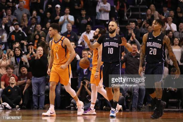 Devin Booker of the Phoenix Suns celebrates ahead of Ricky Rubio and Evan Fournier and Markelle Fultz of the Orlando Magic during the second half of...