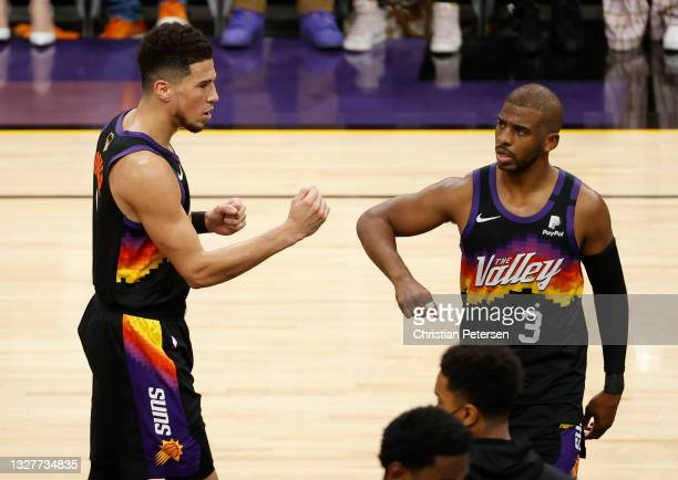 Devin Booker of the Phoenix Suns celebrates with Chris Paul against the Milwaukee Bucks during the first half in Game Two of the NBA Finals at...