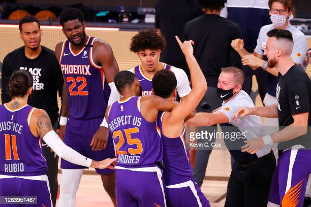 Devin Booker of the Phoenix Suns celebrates with teammates after scoring the game winning basket against the LA Clippers at The Arena at ESPN Wide...