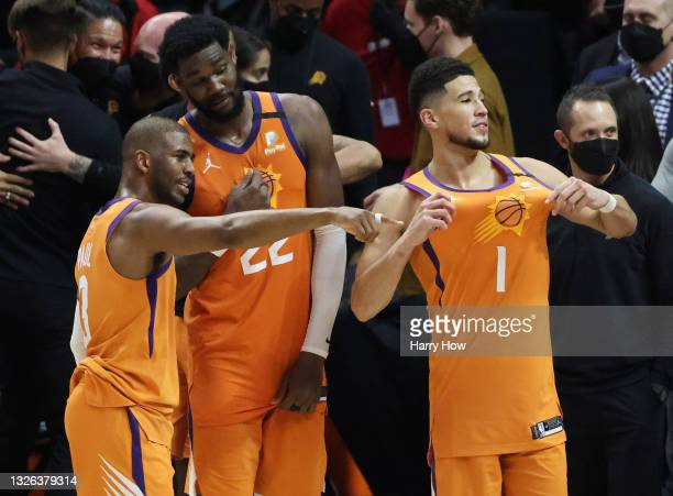 Devin Booker of the Phoenix Suns celebrates with teammates Deandre Ayton and Chris Paul following the team's series win against the LA Clippers in...