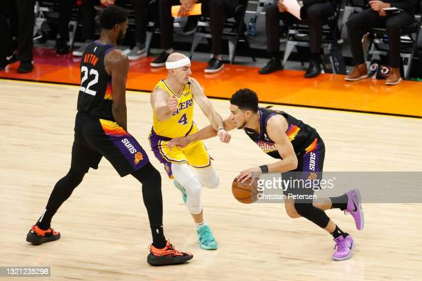 Devin Booker of the Phoenix Suns controls the ball against Alex Caruso of the Los Angeles Lakers during the first half in Game Five of the Western...