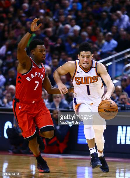 Devin Booker of the Phoenix Suns dribbles the ball as Kyle Lowry of the Toronto Raptors defends during the second half of an NBA game at Air Canada...