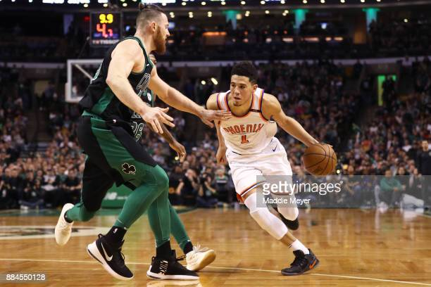 Devin Booker of the Phoenix Suns drives against Aron Baynes of the Boston Celtics during the second half at TD Garden on December 2 2017 in Boston...