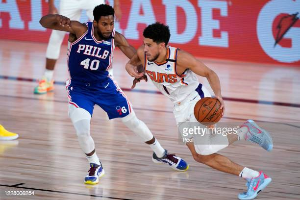 Devin Booker of the Phoenix Suns drives against Glenn Robinson III of the Philadelphia 76ers during the first half of a NBA basketball game at Visa...