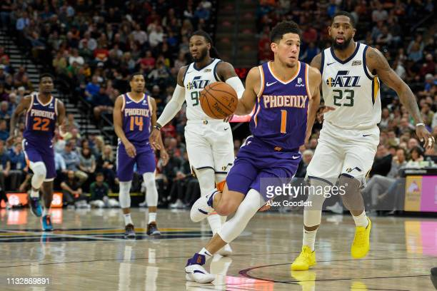 Devin Booker of the Phoenix Suns drives past Royce O'Neale of the Utah Jazz during a game at Vivint Smart Home Arena on March 25 2019 in Salt Lake...