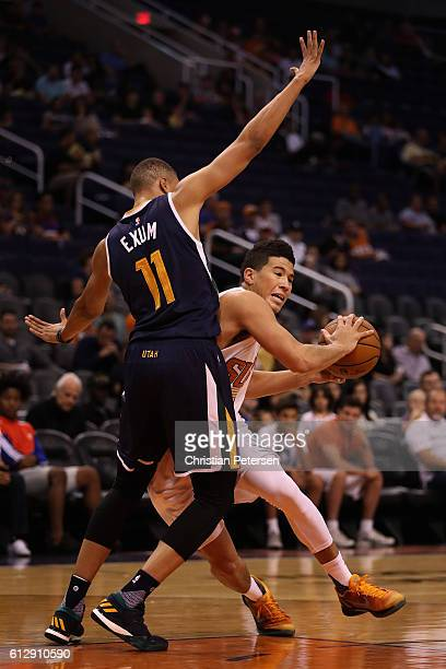 Devin Booker of the Phoenix Suns drives the ball against Dante Exum of the Utah Jazz during the first half of the preseason NBA game at Talking Stick...