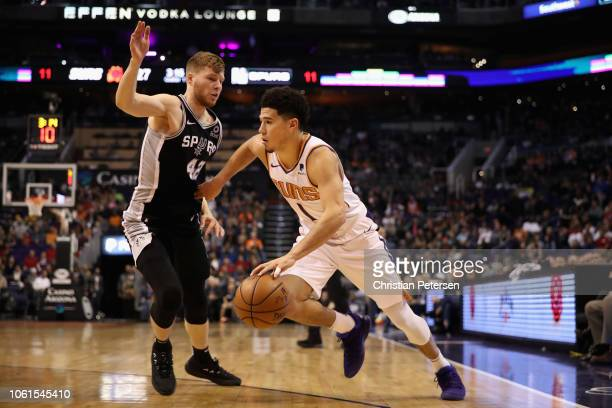 Devin Booker of the Phoenix Suns drives the ball past Davis Bertans of the San Antonio Spurs during the first half of the NBA game at Talking Stick...