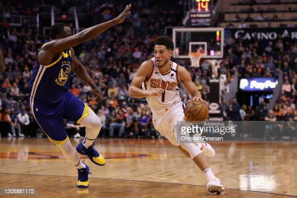 Devin Booker of the Phoenix Suns drives the ball past Draymond Green of the Golden State Warriors during the second half of the NBA game at Talking...