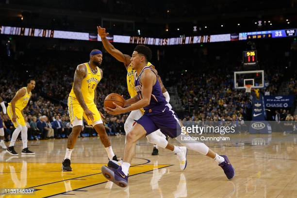 Devin Booker of the Phoenix Suns drives to the basket against Andre Iguodala of the Golden State Warriors at ORACLE Arena on March 10 2019 in Oakland...