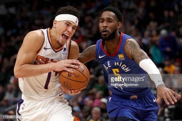 Devin Booker of the Phoenix Suns drives to the basket against Will Barton of the Denver Nuggets in the first quarter at the Pepsi Center on January...