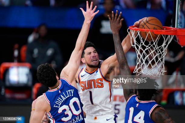 Devin Booker of the Phoenix Suns dunks the ball against Furkan Korkmaz and Norvel Pelle of the Philadelphia 76ers during the second half of an NBA...