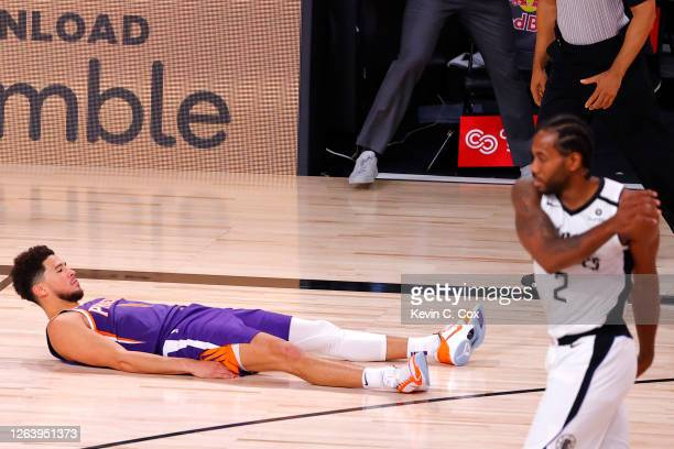 Devin Booker of the Phoenix Suns falls to the ground after scoring the game winning basket against the LA Clippers at The Arena at ESPN Wide World Of...
