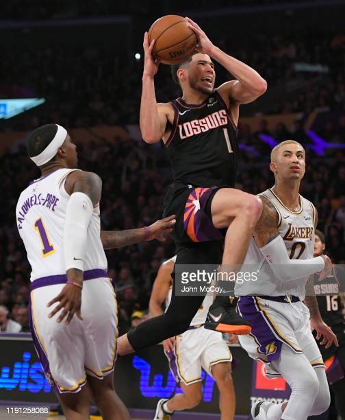 Devin Booker of the Phoenix Suns gets past Kentavious CaldwellPope and Kyle Kuzma of the Los Angeles Lakers in the second half at Staples Center on...