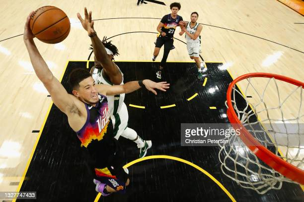 Devin Booker of the Phoenix Suns goes up for a slam dunk ahead of Jrue Holiday of the Milwaukee Bucks in the first half of game two of the NBA Finals...