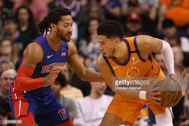 Devin Booker of the Phoenix Suns handles the ball against Derrick Rose of the Detroit Pistons during the first half of the NBA game at Talking Stick...