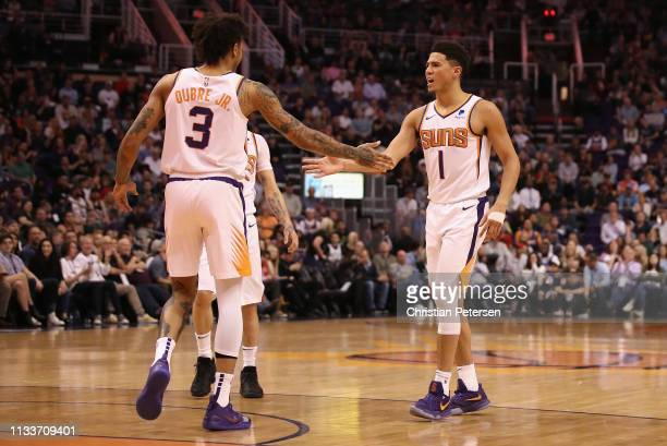 Devin Booker of the Phoenix Suns high fives Kelly Oubre Jr #3 after scoring against the Milwaukee Bucks during the first half of the NBA game at...