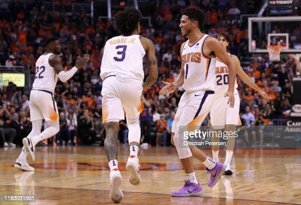 Devin Booker of the Phoenix Suns high fives Kelly Oubre Jr #3 after scoring against the Sacramento Kings during the second half of the NBA game at...