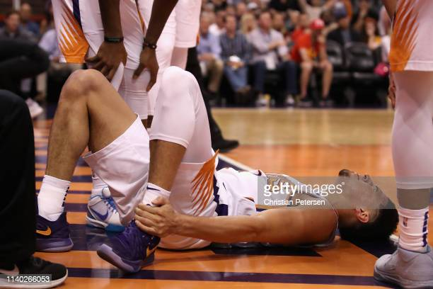 Devin Booker of the Phoenix Suns holds his ankle after an injury during the first half of the NBA game against the Utah Jazz at Talking Stick Resort...