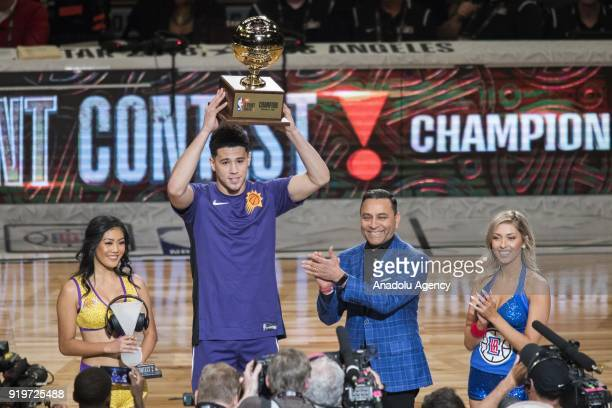 Devin Booker of the Phoenix Suns holds the trophy after winning the JBL ThreePoint Contest during State Farm AllStar Saturday Night as part of...