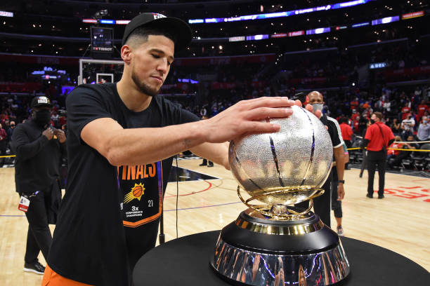 Devin Booker of the Phoenix Suns holds the Western Conference Finals Trophy after the game against the LA Clippers during Game 6 of the Western...