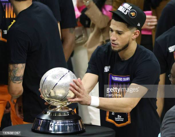 Devin Booker of the Phoenix Suns holds the Western Conference Championship trophy after the Suns defeated the LA Clippers in Game Six of the Western...