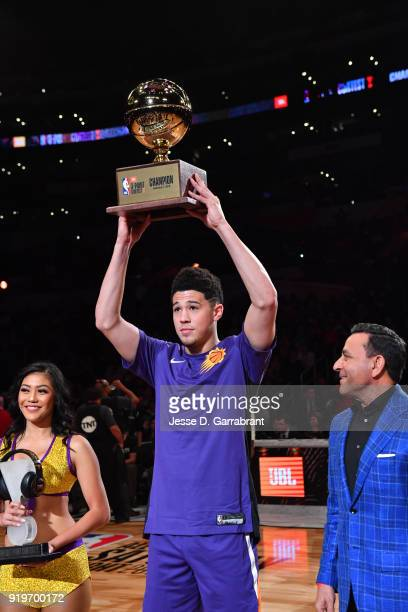 Devin Booker of the Phoenix Suns holds up the trophy after winning the threepoint contest during the JBL ThreePoint Contest during State Farm AllStar...