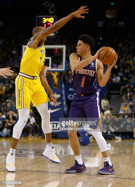 Devin Booker of the Phoenix Suns is defended by Andre Iguodala of the Golden State Warriors at ORACLE Arena on March 10 2019 in Oakland California...