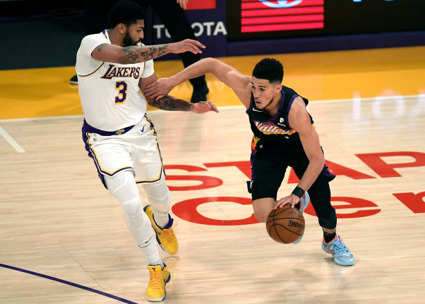 Devin Booker of the Phoenix Suns is defended by Anthony Davis of the Los Angeles Lakers during the first half at Staples Center on May 9, 2021 in Los...
