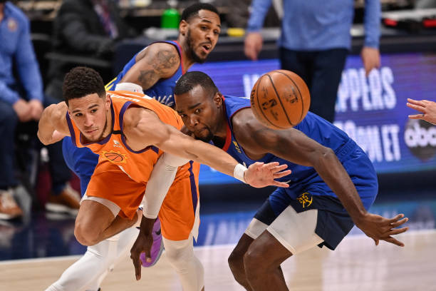 Devin Booker of the Phoenix Suns is defended by Paul Millsap of the Denver Nuggets in Game Three of the Western Conference second-round playoff...