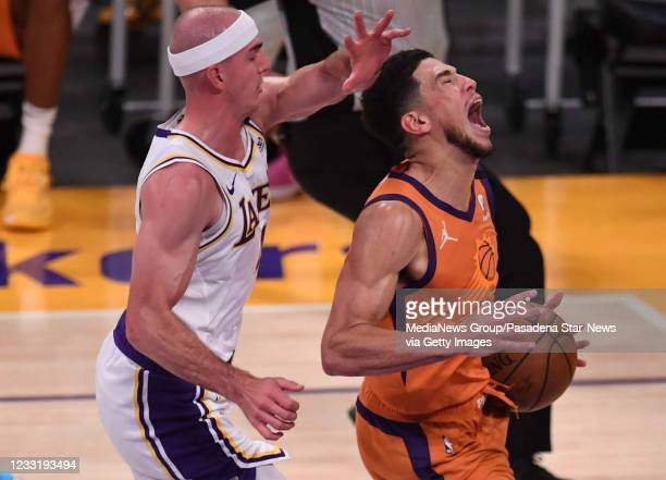 Devin Booker of the Phoenix Suns is fouled by Alex Caruso of the Los Angeles Lakers in the second half of game four of the Western Conference First...