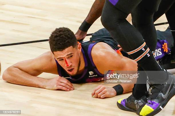 Devin Booker of the Phoenix Suns is injured from a headbutt during the third quarter in game two of the NBA Western Conference finals against the LA...