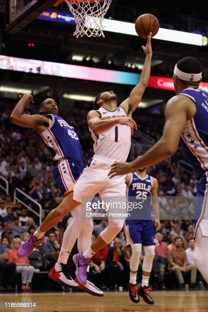 Devin Booker of the Phoenix Suns lays up a shot past Al Horford of the Philadelphia 76ers during the second half of the NBA game at Talking Stick...