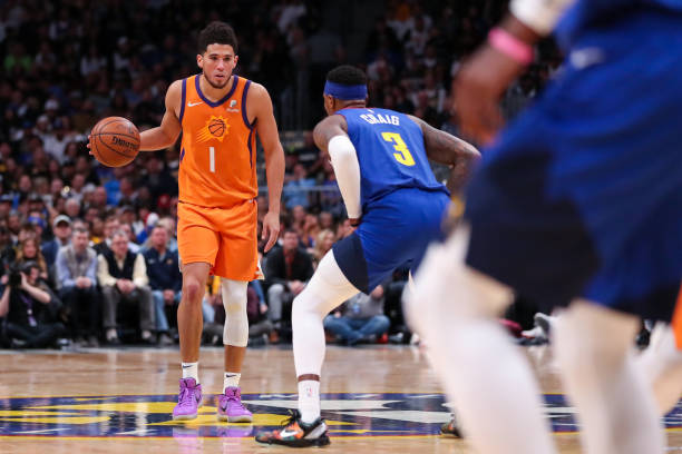 Devin Booker of the Phoenix Suns looks past the defense of Torrey Craig of the Denver Nuggets at Pepsi Center on October 25, 2019 in Denver,...