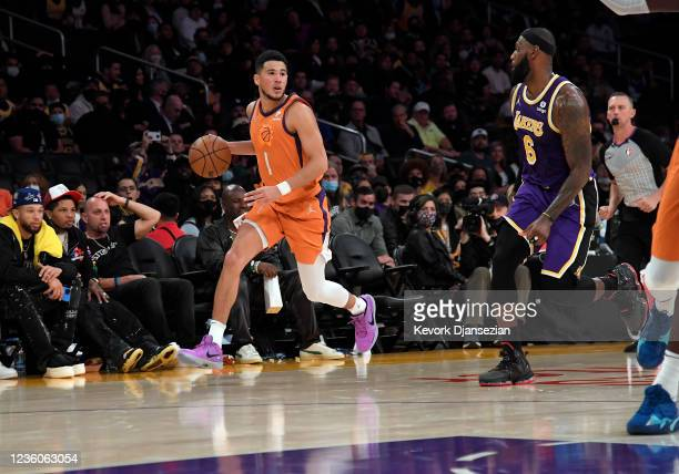 Devin Booker of the Phoenix Suns looks to pass against LeBron James of the Los Angeles Lakers during the second half against at Staples Center on...