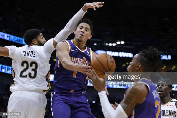 767c03e5003bf Devin Booker of the Phoenix Suns passes the ball to Richaun Holmes as Anthony  Davis of