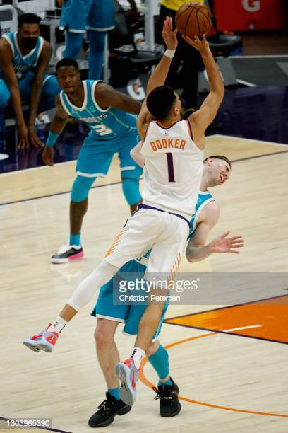 Devin Booker of the Phoenix Suns puts up a three-point shot and draws a foul from Gordon Hayward of the Charlotte Hornets during the final moments of...