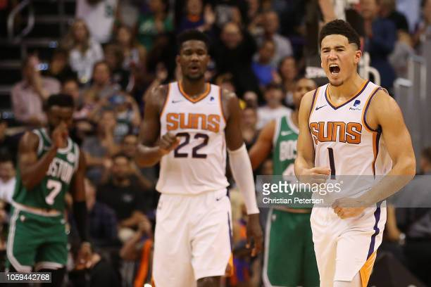 Devin Booker of the Phoenix Suns reacts alongside Deandre Ayton after scoring against the Boston Celtics during the second half of the NBA game at...