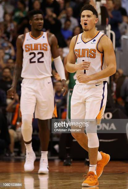 Devin Booker of the Phoenix Suns reacts alongside Deandre Ayton during the NBA game against the Boston Celtics at Talking Stick Resort Arena on...