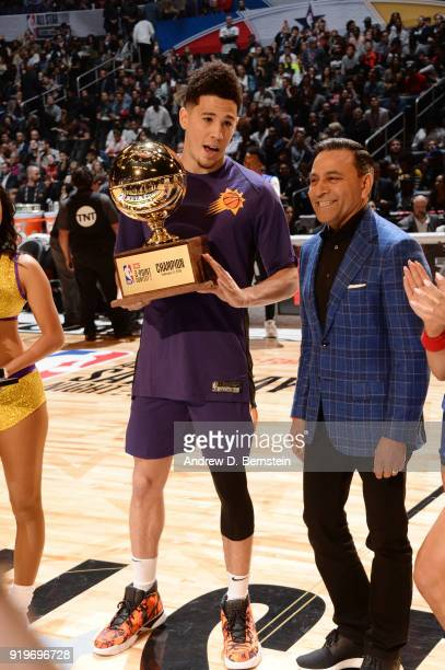Devin Booker of the Phoenix Suns receives the champions trophy during the JBL ThreePoint Contest during State Farm AllStar Saturday Night as part of...