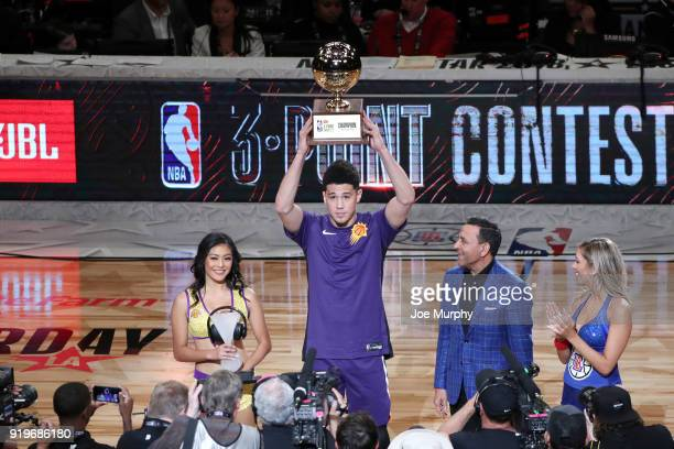 Devin Booker of the Phoenix Suns receives the JBL ThreePoint Contest Trophy during State Farm AllStar Saturday Night as part of the 2018 NBA AllStar...