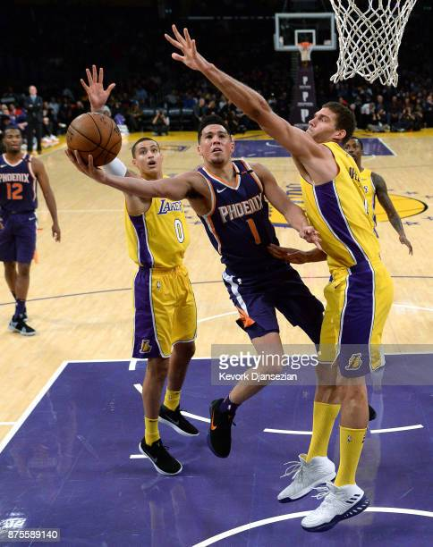 Devin Booker of the Phoenix Suns scores a basket against Brook Lopez and Kyle Kuzma of the Los Angeles Lakers during the first half a basketball game...