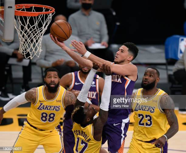 Devin Booker of the Phoenix Suns scores on a layup over Dennis Schroder of the Los Angeles Lakers as LeBron James and Markieff Morris look on during...