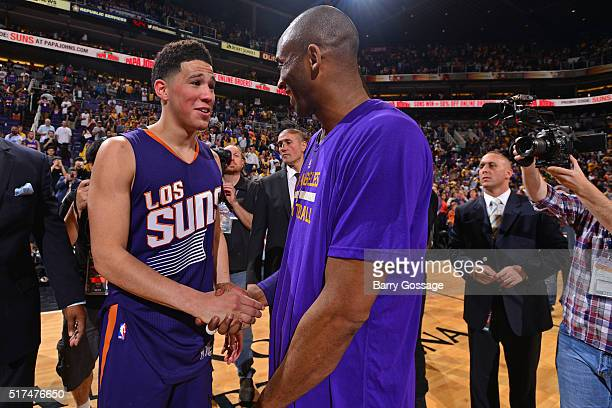 Devin Booker of the Phoenix Suns shakes hands with Kobe Bryant of the Los Angeles Lakers after the game at Talking Stick Resort Arena on March 23...