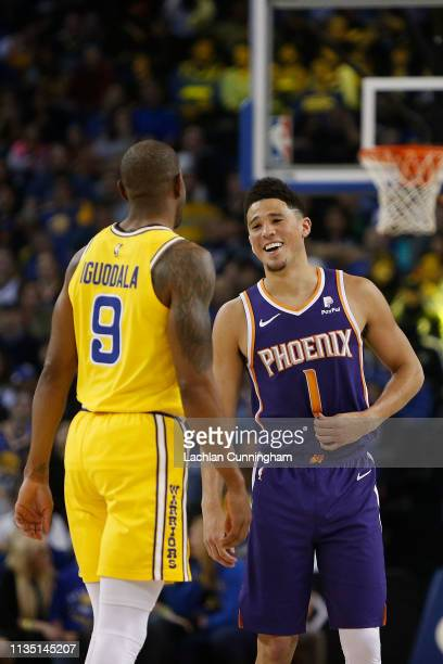 Devin Booker of the Phoenix Suns shares a laugh with Andre Iguodala of the Golden State Warriors during the game at ORACLE Arena on March 10 2019 in...