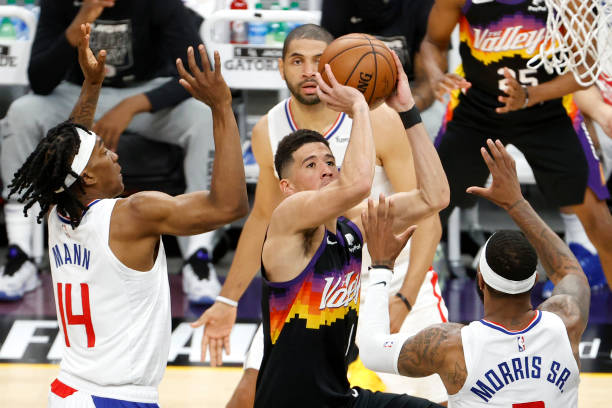 Devin Booker of the Phoenix Suns shoots against Terance Mann and Marcus Morris Sr. #8 of the Los Angeles Clippers in the second quarter during game...