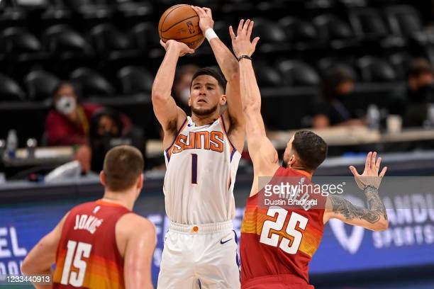 Devin Booker of the Phoenix Suns shoots and scores under coverage by Austin Rivers of the Denver Nuggets in Game Four of the Western Conference...