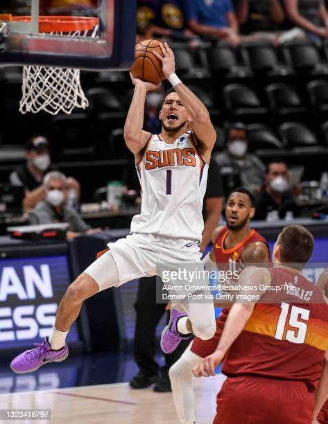 Devin Booker of the Phoenix Suns shoots as Nikola Jokic of the Denver Nuggets defends during the second quarter at Ball Arena on Sunday, June 13,...